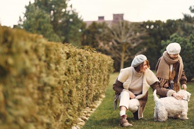 Мать с дочерью гуляет с собакой