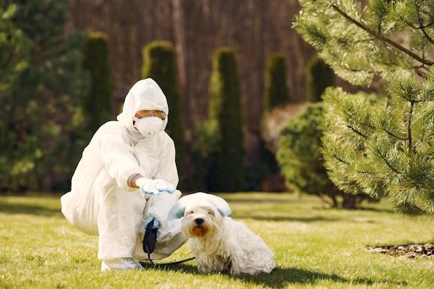 犬と一緒に歩いて防護服の女性