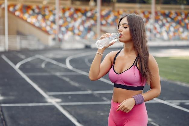 Спортивная девушка в розовой форме тренируется на стадионе