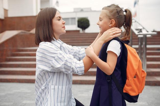 母は小さな娘を学校に準備します
