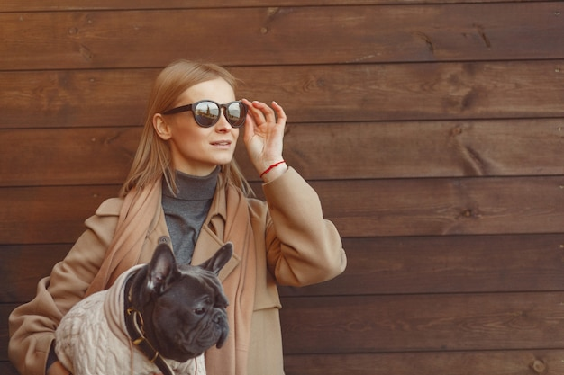 黒いブルドッグと茶色のコートを着たエレガントな女性