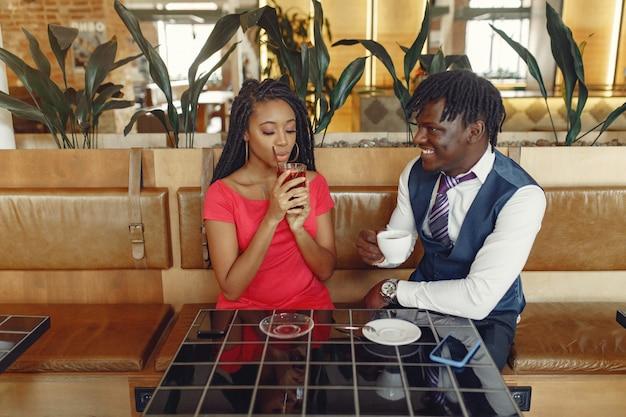 スタイリッシュな黒のカップルがカフェに座って、コーヒーを飲む