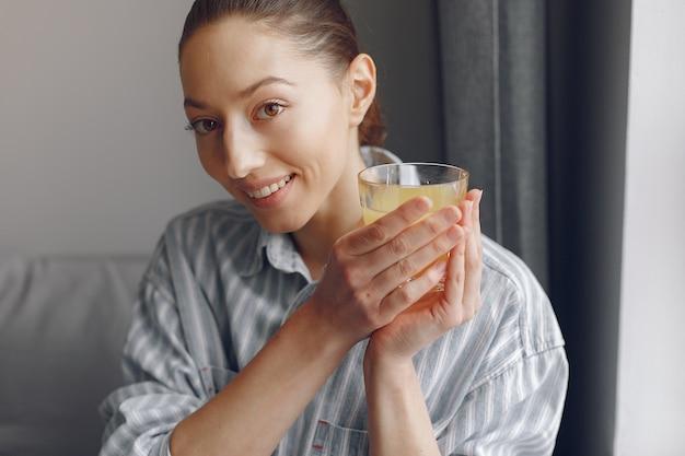Красивая девушка дома с соком апельсина