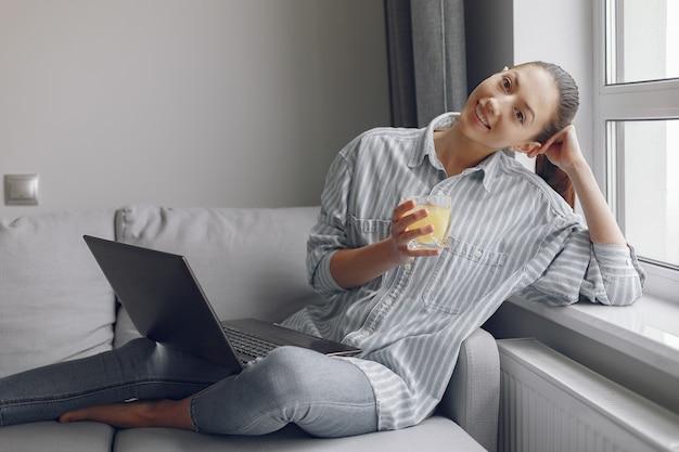 Девушка сидит дома и использует ноутбук