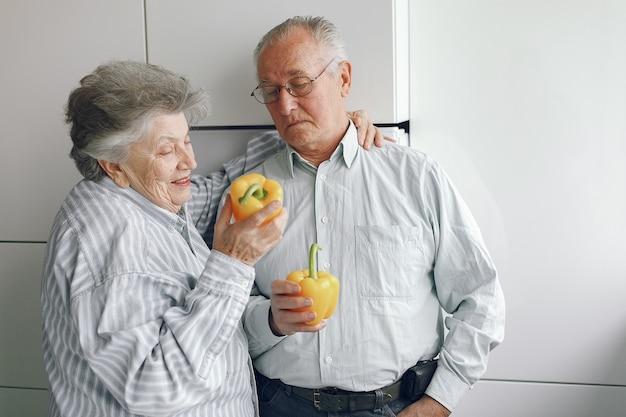 美しい老夫婦が台所で料理を準備します。