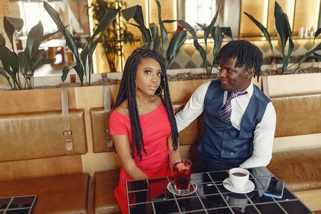 Стильная черная пара сидит в кафе и пьет кофе