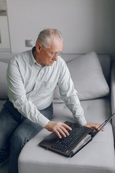 Элегантный старик сидит дома и использует ноутбук