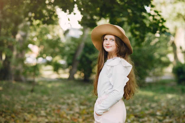 Маленькая девочка в парке стоит в парке в коричневой шляпе