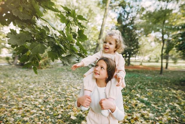 Симпатичные маленькие сестры играют в весеннем парке
