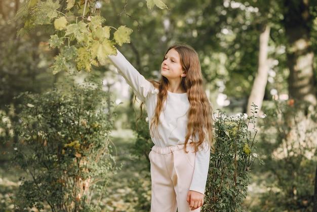 Маленькая девочка в парке в белой блузке