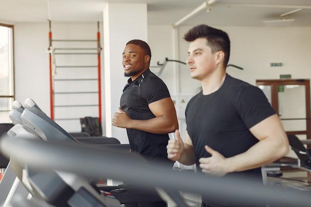 Двое интернациональных друзей занимаются в спортзале
