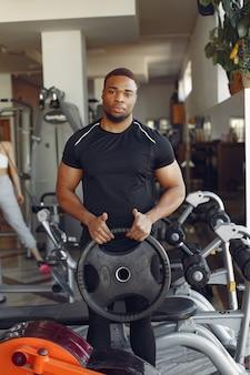 Красивый черный человек занимается в тренажерном зале