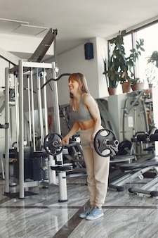 Красивая девушка занимается в спортзале со штангой