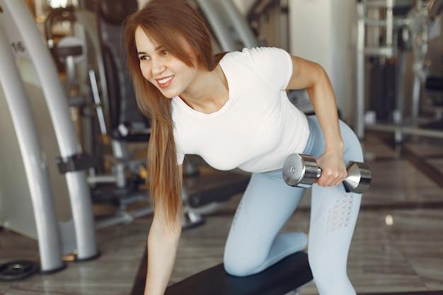 Красивая девушка занимается в тренажерном зале с гантелями