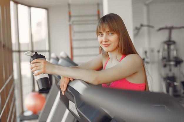 Красивая девушка в спортзале на беговой дорожке