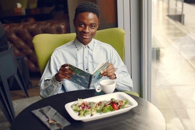 Черный человек сидит в кафе и ест овощной салат