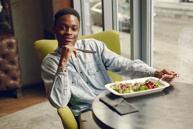 カフェに座っていると野菜のサラダを食べる黒人男性