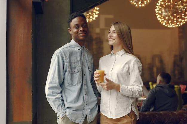 Международные люди стоят в кафе с апельсиновым соком