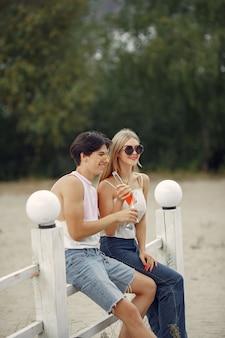 Пара веселится на пляже с напитками