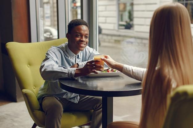 カフェに立ってジュースを飲む国際人