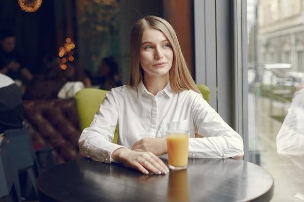 白いブラウスでエレガントな女性がカフェで時間を過ごす