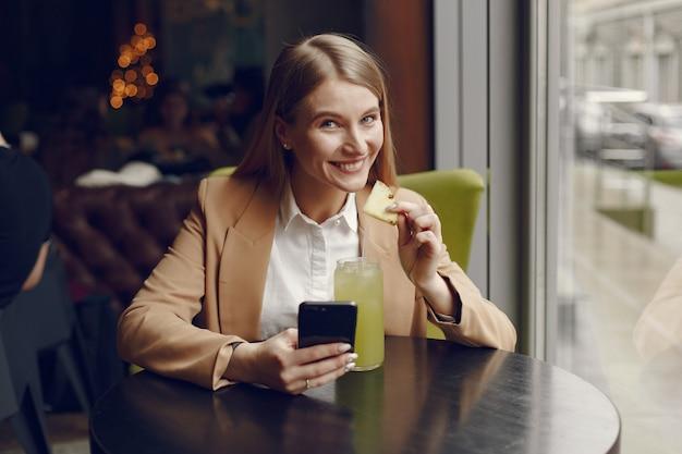 Элегантная женщина, сидя за столом с коктейлем и телефоном
