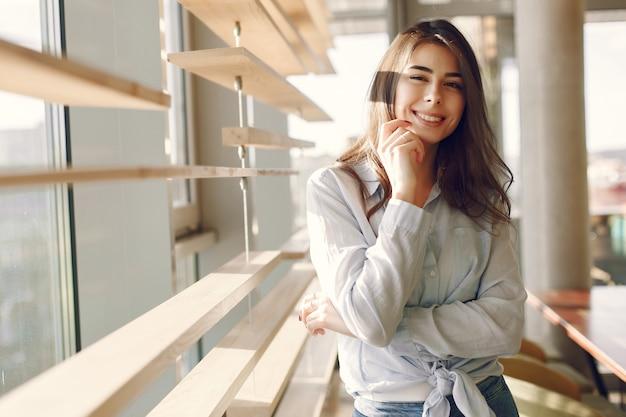 Улыбающаяся девушка в синей рубашке стоит возле окна и позирует