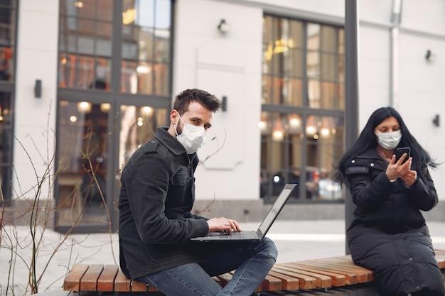 電子機器を使用して都市に座っている防護マスクを着ている人