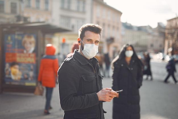 通りに立っている防護マスクを着ている人
