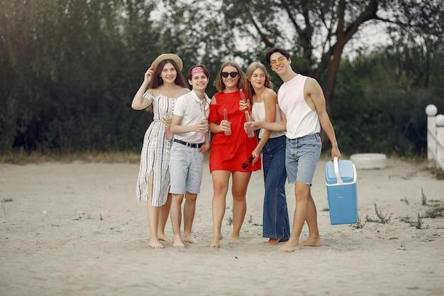 Друзья веселятся на пляже с напитками
