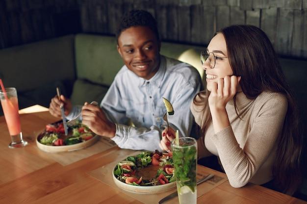 サラダやカクテルでテーブルに座っている国際人