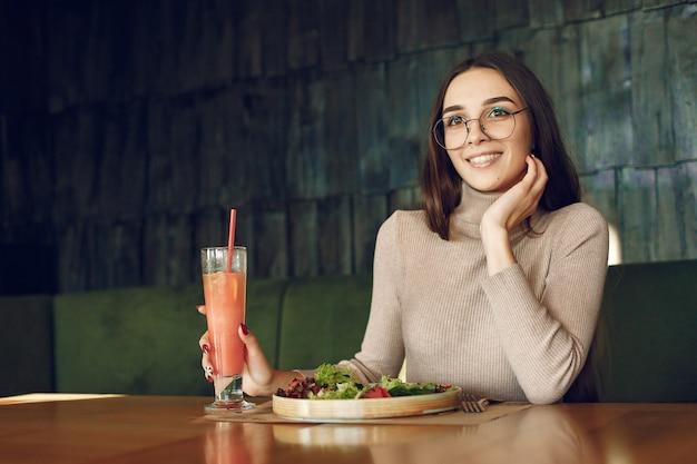 カクテルとサラダのテーブルに座っているエレガントな女性