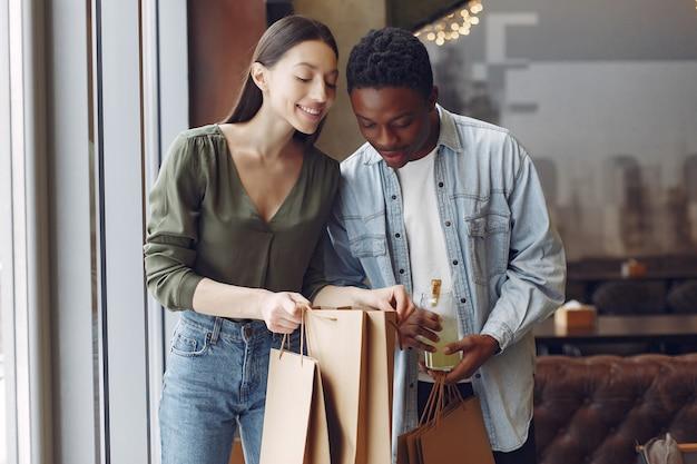 買い物袋のあるカフェに立っている国際人
