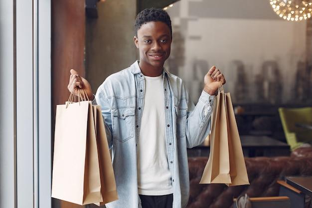 ショッピングバッグ付きのカフェに立っている黒人男性