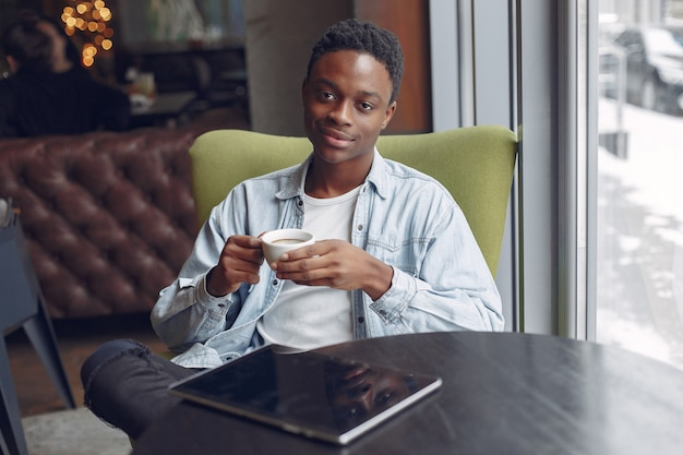 カフェに座ってコーヒーを飲む黒人男性