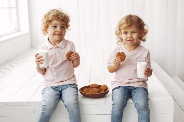 クッキーを食べて牛乳を飲むかわいい子供たち