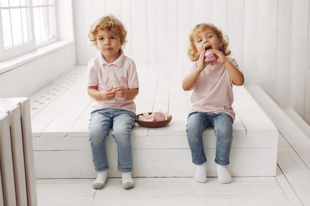 Милые дети едят печенье дома