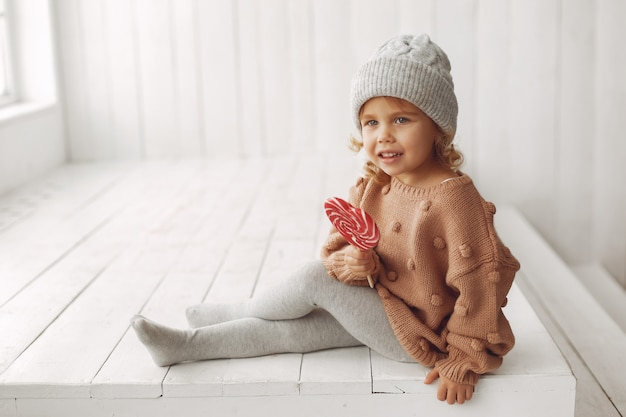 Милая маленькая девочка сидит и ест конфеты
