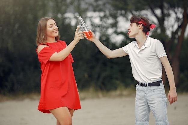 ドリンクを飲みながらビーチで楽しんでいるカップル