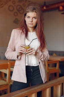 Элегантная женщина в розовой куртке проводит время в кафе