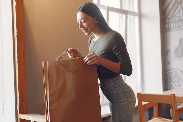 買い物袋付きのカフェに立っているスタイリッシュな女の子
