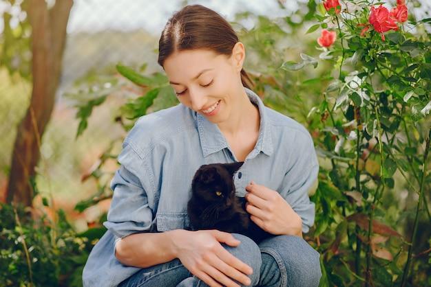 Женщина в синей рубашке играет с милой кошечкой