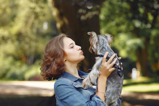 Милая девушка в синем пиджаке играет с маленькой собачкой