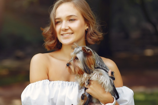 Милая девушка в белой блузке играет с маленькой собачкой