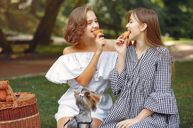 Милые девушки в парке играют с маленькой собачкой