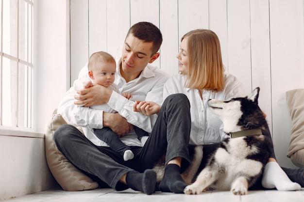 Красивая семья проводит время в спальне с собакой