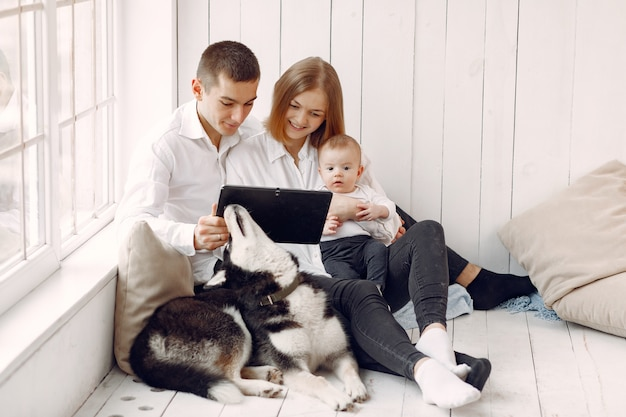 美しい家族がタブレットで寝室で時間を過ごす