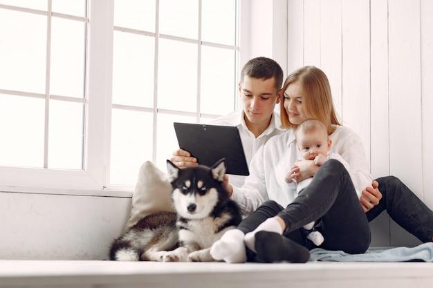 Красивая семья проводит время в спальне с планшетом