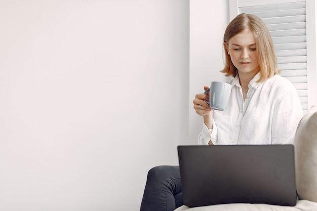 自宅で座っているとラップトップを使用して女性