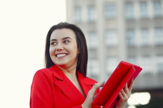 タブレットを使用して赤いジャケットの女性